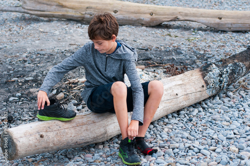 Child Sitting On A Rocky Beach Putting His Shoes