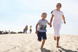 Fototapeta Fototapety z morzem do Twojej sypialni - Słoneczne wakacje. Dzieci biegną po plaży