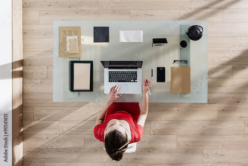 Fotografía  top view, a woman sitting at tidy desk and working on her laptop