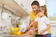Little girl and her dad cutting and preparing fresh fruit and vegetables for breakfast in the kitchen.