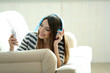 Woman listening music in headphones in room
