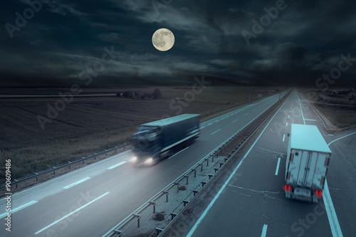 Foto auf Leinwand Nacht-Autobahn Blue and white truck in motion blur at midnight