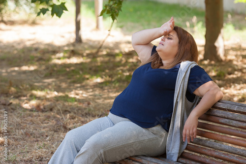 Valokuva  Fatigued overweight woman sitting on a bench