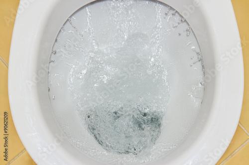 Photo  Closeup view of a flushing white toilet