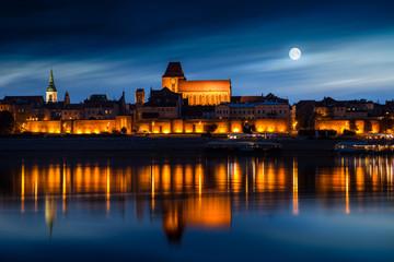 Fototapeta Old town reflected in river at sunset. Torun, Poland.