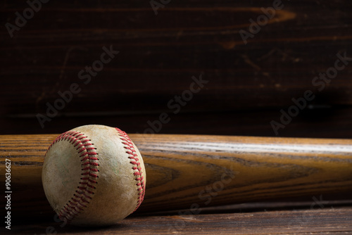 A wooden baseball bat and ball on a wooden background Poster