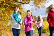 Mädchen rennen bei Familien Spaziergang im Herbst Park vorweg