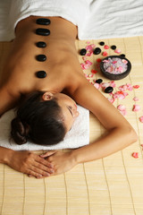 Fototapeta samoprzylepna Young woman with pebbles on her back on massage table in beauty spa salon