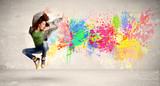 Fototapeta Młodzieżowe - Happy teenager jumping with colorful ink splatter on urban backg