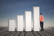 Young businessman standing next to growing bar chart