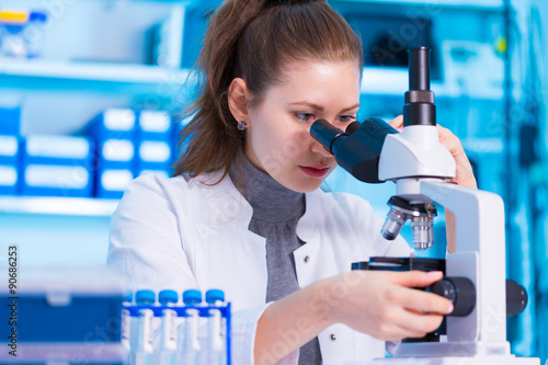 Fotografia  Female scientist looking through a microscope in laboratory