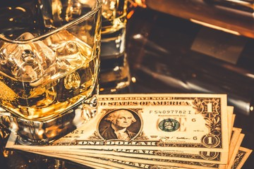 glasses of whiskey near bottle on dollars money on a black table. Old western theme style