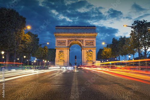 Spoed Foto op Canvas Parijs Arc de Triomphe. Image of the iconic Arc de Triomphe in Paris city during twilight blue hour.