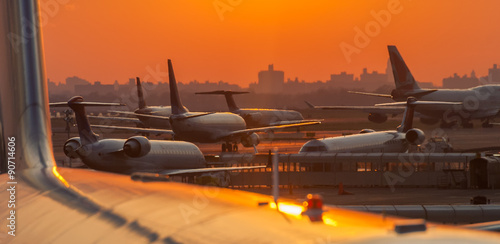 Sunset at the airport with airplanes ready to take off - 90714606