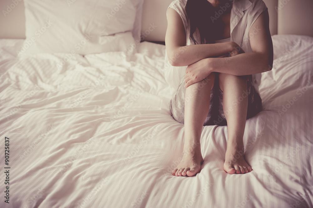 Fototapeta ベッドの上で三角座りをする女性