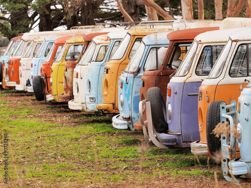 Fényképezés  Row of defunct colorful and run down desolate vans of all the same Volkswagen Bu