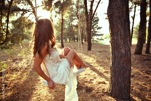 Young woman is swinging on a swing in summer pine forest. Image
