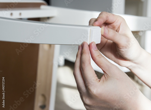Foto  Young woman are sticking floor care pad at chair legs