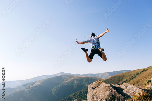 man jumps from the cliff in mountains Wallpaper Mural