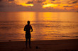 Silhouetted of man on the beach at the sunset time.