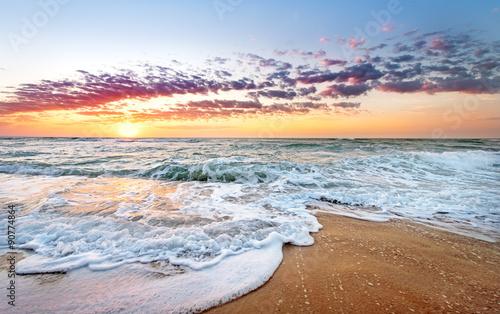 Fotomural Colorful ocean beach sunrise with deep blue sky and sun rays.