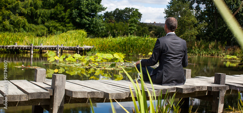 corporate green break - meditating middle age male professional sitting on a wooden bridge in the middle of an asian-like green pond for company wellbeing,back view with park foreground