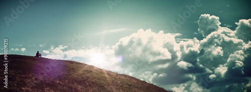Obraz Solitary Person Sitting on Hill Watching Sunrise - fototapety do salonu