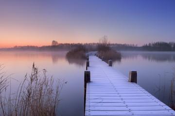 Fototapeta Zima Boardwalk on a lake at dawn in winter, The Netherlands