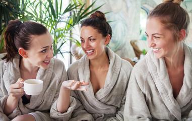 Fototapeta samoprzylepna Three young women drinking tea at spa resort