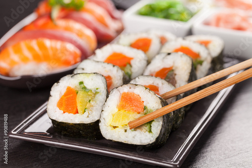 Obraz sushi pieces with chopsticks - fototapety do salonu