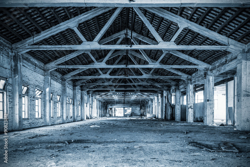Spoed Foto op Canvas Industrial geb. Empty industrial loft in an architectural background with bare cement walls, floors and pillars supporting a mezzanine blue tone