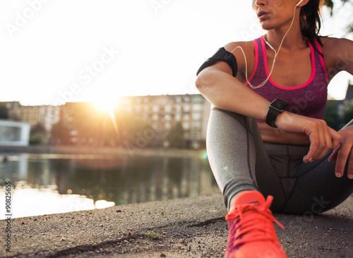 Fotografía  Young woman runner resting along pond