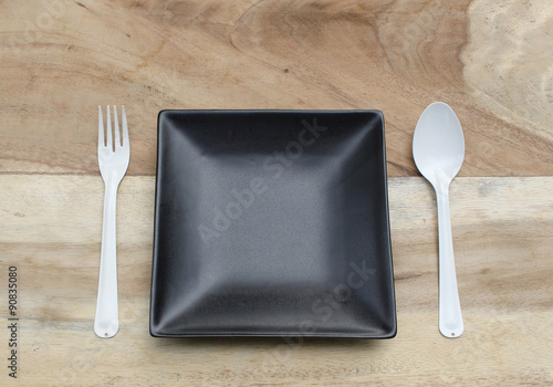 empty plate with spoon and fork ,top view. on wood background
