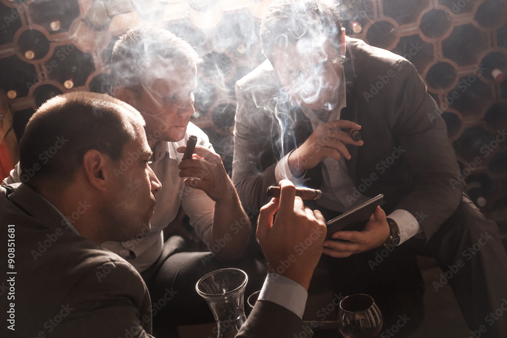 Fototapeta Three businessmen sitting in the wine cellar drinking wine and smoke cigar, resting after a hard day at work.