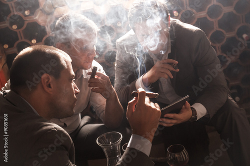 Fotografie, Tablou Three businessmen sitting in the wine cellar drinking wine and smoke cigar, resting after a hard day at work