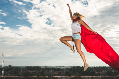 Photo  Blonde woman in red dress and red mantle jumping outdoor as a superhero against