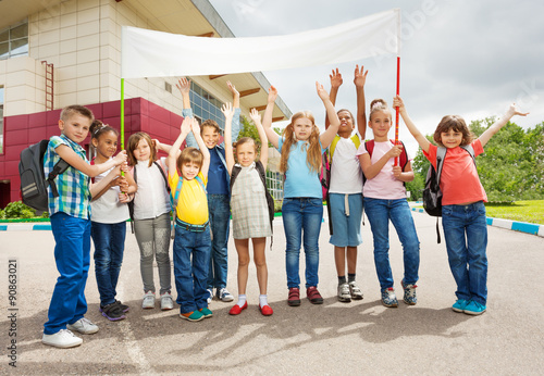 Photo Group of happy children with arms up hold placard