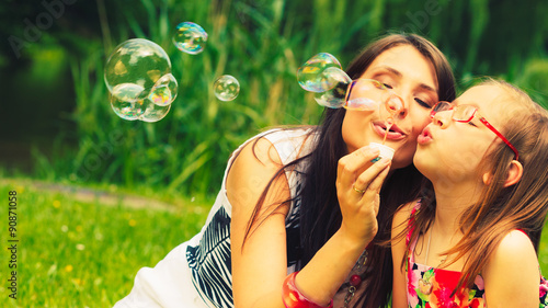 Fototapeta Mother and child blowing soap bubbles outdoor. obraz