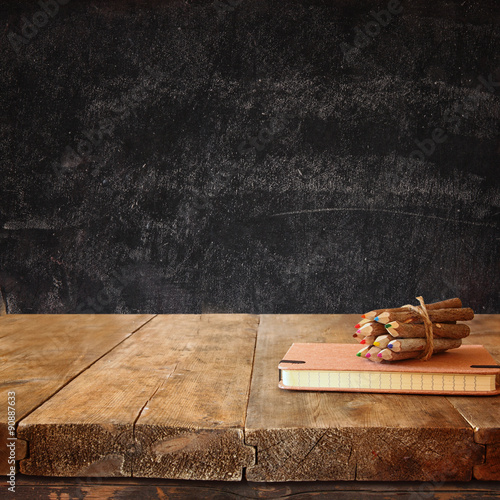 vintage notebook and stack of wooden colorful pencils on wooden textures table Poster