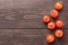 Fresh Tomato On The Brown Wooden Background. Top View