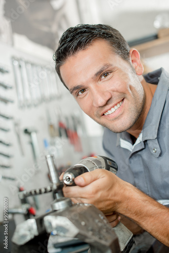 Mechanic holding drill Tablou Canvas