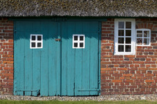 A Pattern Of Windows. An Old Traditional Farmhouse In Denmark, Complete With Thatched Roof. The Old Windows Form A Repetitive Pattern And The Red Brick Contrasts With The Teal Wooden Barn Doors.