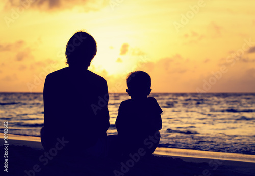 Obraz father and little son looking at sunset on beach - fototapety do salonu