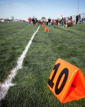 Yard Marker On American Football Field With Blurred People In Background