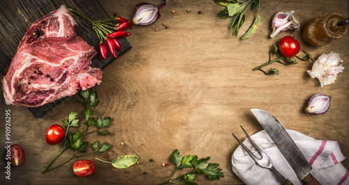 Staande foto Vlees Pork kotelett with fresh ingredients for cooking - herbs,spices and tomatoes. Vintage kitchen tools - fork and meat knife. Rustic wooden backgound, top view, frame