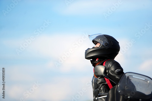 obraz dibond The girl motorcyclist sits on the motorcycle in a helmet