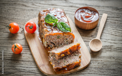 Photo  Meat loaf with barbecue sauce on the wooden board
