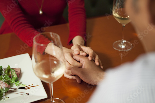 Fotografie, Obraz  The couple are holding hands on the table
