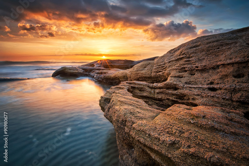 Spoed Foto op Canvas Cappuccino Rocky sunrise. Sea sunrise at the Black Sea coast near Ravda, Bulgaria