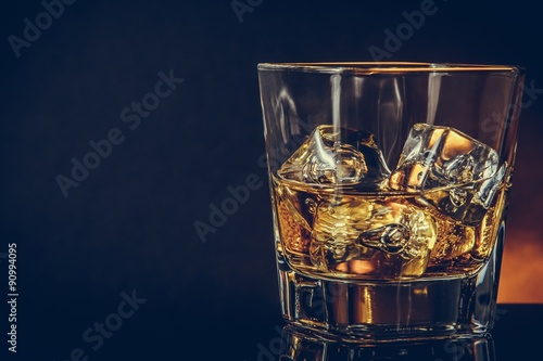 Photo glass of whiskey on black background with reflection, warm atmosphere